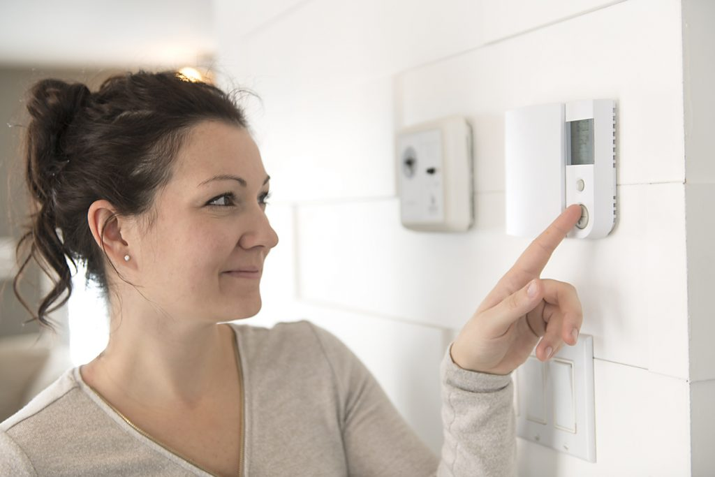 Woman adjusts thermostat setting
